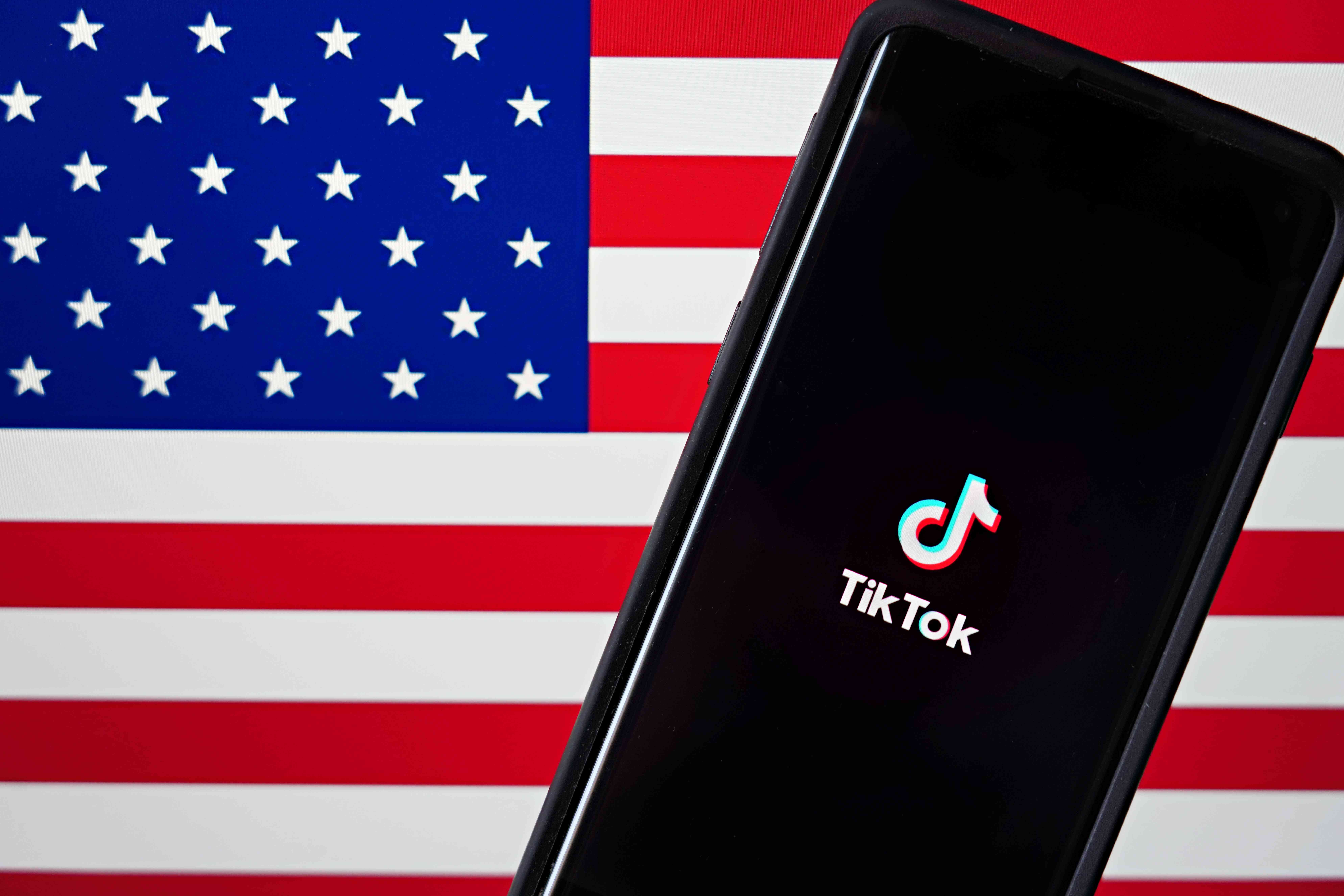 A mobile phone featuring the TikTok app is displayed next to the American flag
