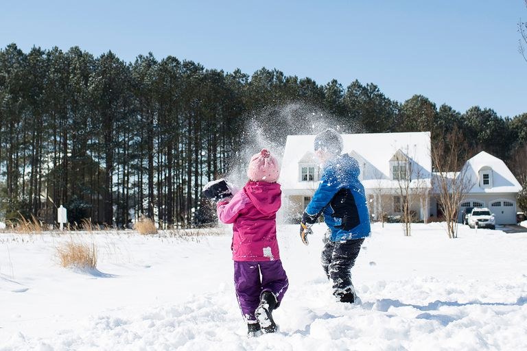 Siblings playing with snow on field against clear sky