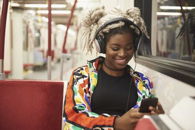 Commuting to work and listening to headphones in subway