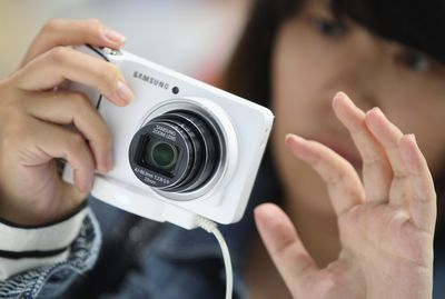 Person holding a Samsung point-and-shoot camera