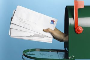 A hand holding envelopes sticks out from inside a mailbox
