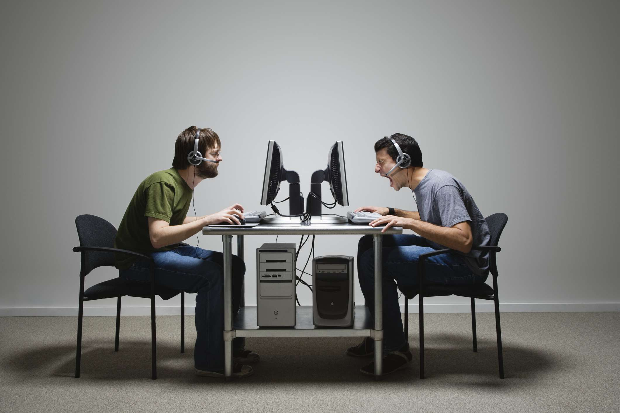 A profile of two men using computers sitting opposite to each other at a desk