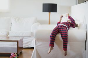 Child in pajamas lying on couch armrest with mobile device in two hands.