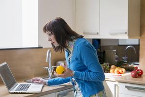 Woman using laptop while cooking