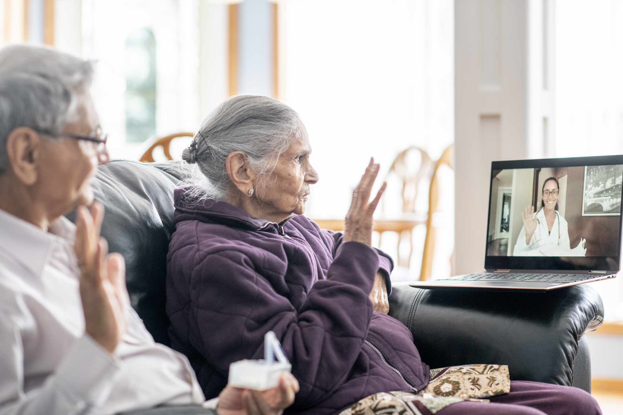 An elderly couple having a consultation with a Virtual Reality healthcare professional.