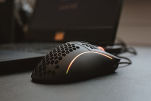 Close-up of a computer mouse, next to a laptop.