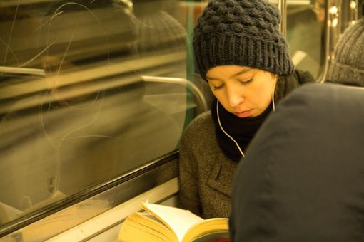Woman reading a book on a train wearing noise canceling earbuds.