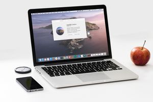 Macbook with macOS Catalina on a table with a phone and apple.