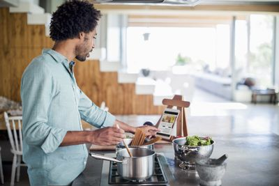 Man cooking using a tablet for recipes