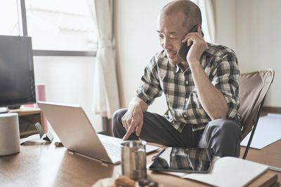 A man sitting on a couch looking at his laptop while holding a phone