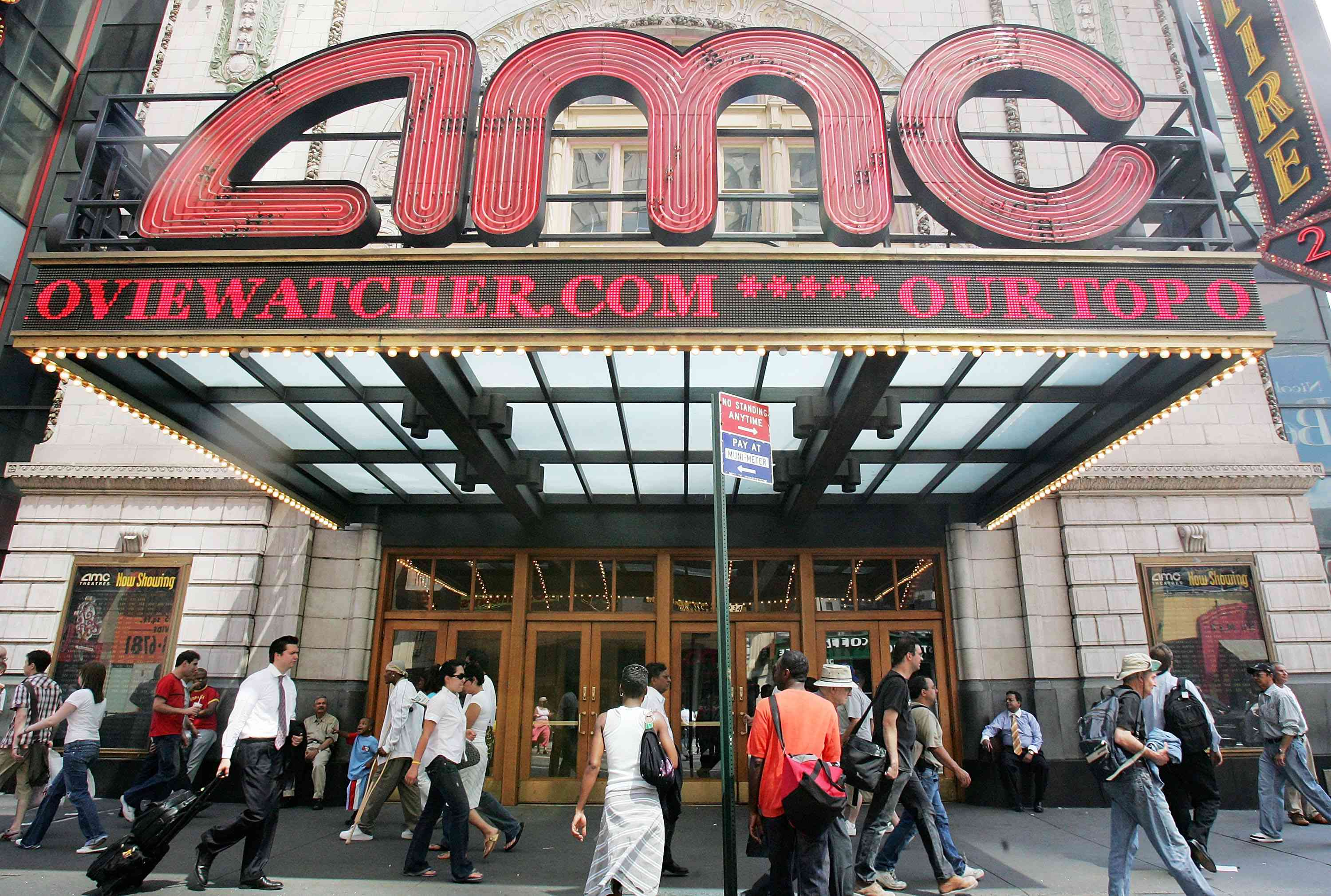 Pedestrians pass an AMC movie theater in Times Square