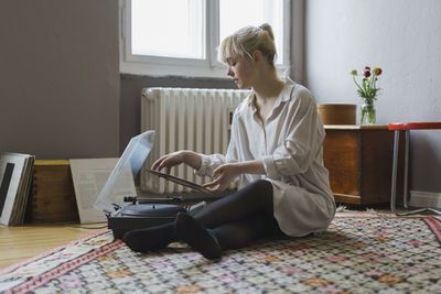 Woman using turntable in living room