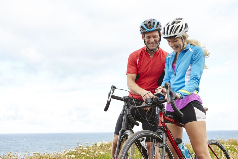 An athletic couple using a GPS app on their iPhone during a bike ride.