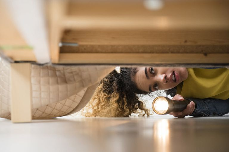 Woman searching under a bed with a flashlight