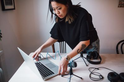 Female blogger using laptop standing by table with microphone at home