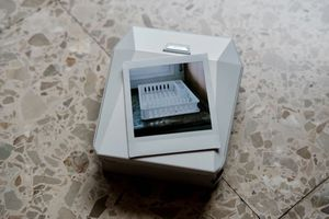 B&W photo of a basket resting on top of Fujifilm's Instax printer