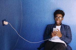 Young man charging phone at library