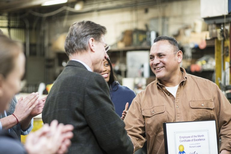 Worker receiving award in workshop.