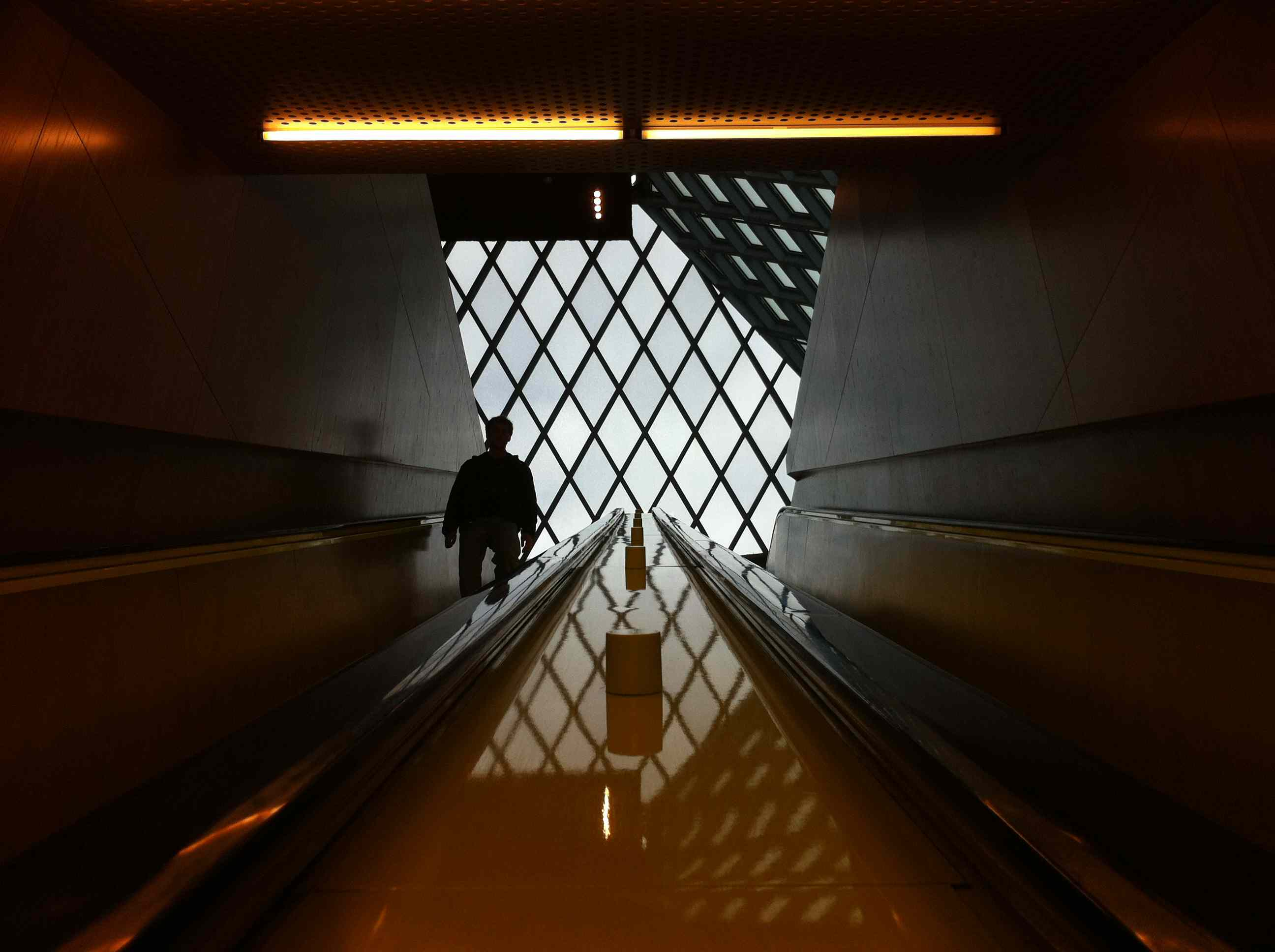 Man going down an escalator in a dark hallway