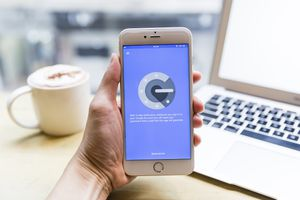 Google Authenticator is open on an iPhone held in a pale hand.