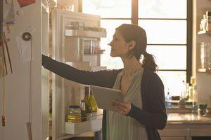 Woman holding an iPad while browsing the fridge