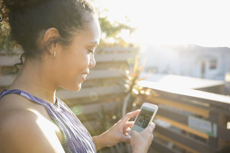 Woman using smart phone on sunny deck