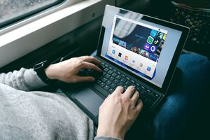 A man sitting on a train loading Android apps from the Microsoft Store on his Windows 11 Surface Pro.