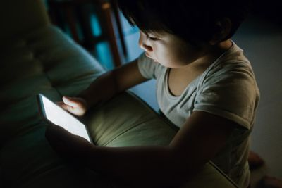 Little kid concentrated on playing with smartphone in the dark