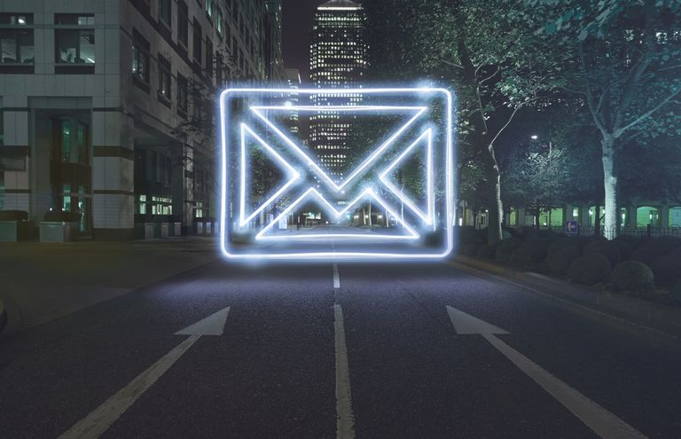 Neon envelope symbol in one way street at night