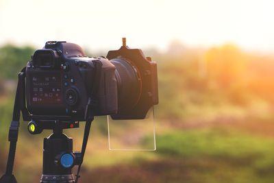 Photography camera set on tripod at sunset