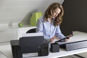 A woman in an office printing something from an Android tablet.