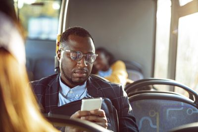 A man sitting on a bus looking at his smartphone