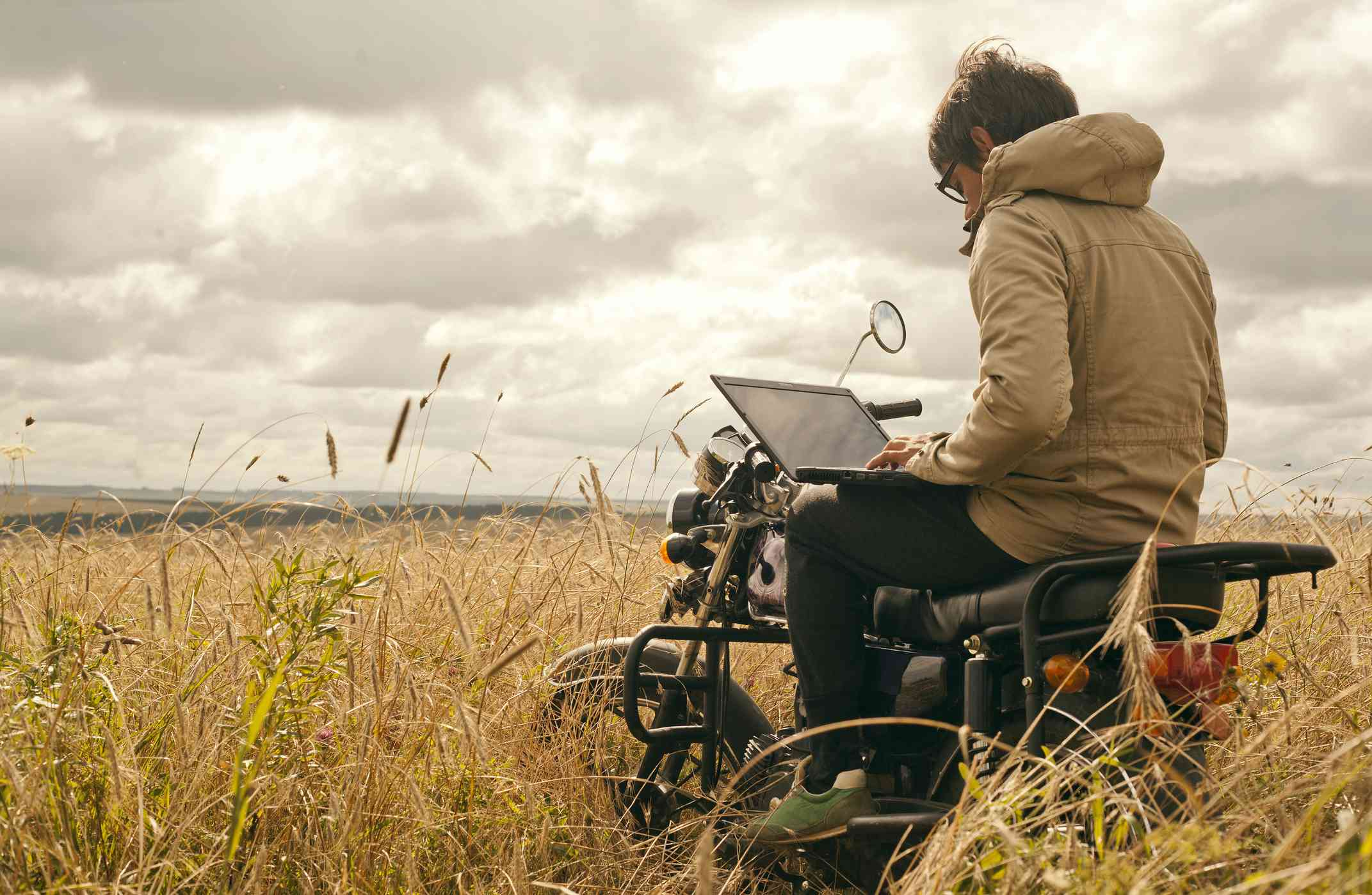 Someone using a laptop while sitting on a motorbike in the middle of a rural field.