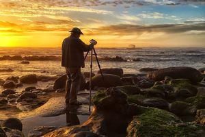A photographer composing a sunset scene at a beach