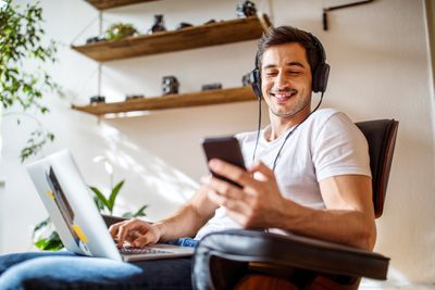 Man with Phone and Laptop Listening to Music