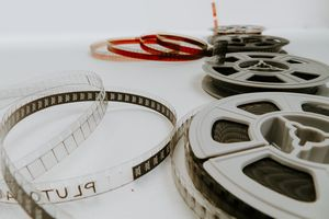 A photo of four 8mm film reels laid out on a white table.