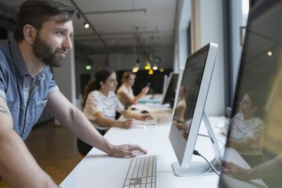 Businessman using computer at counter in open plan office