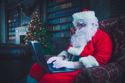 Santa Claus sitting in a chair using a laptop computer