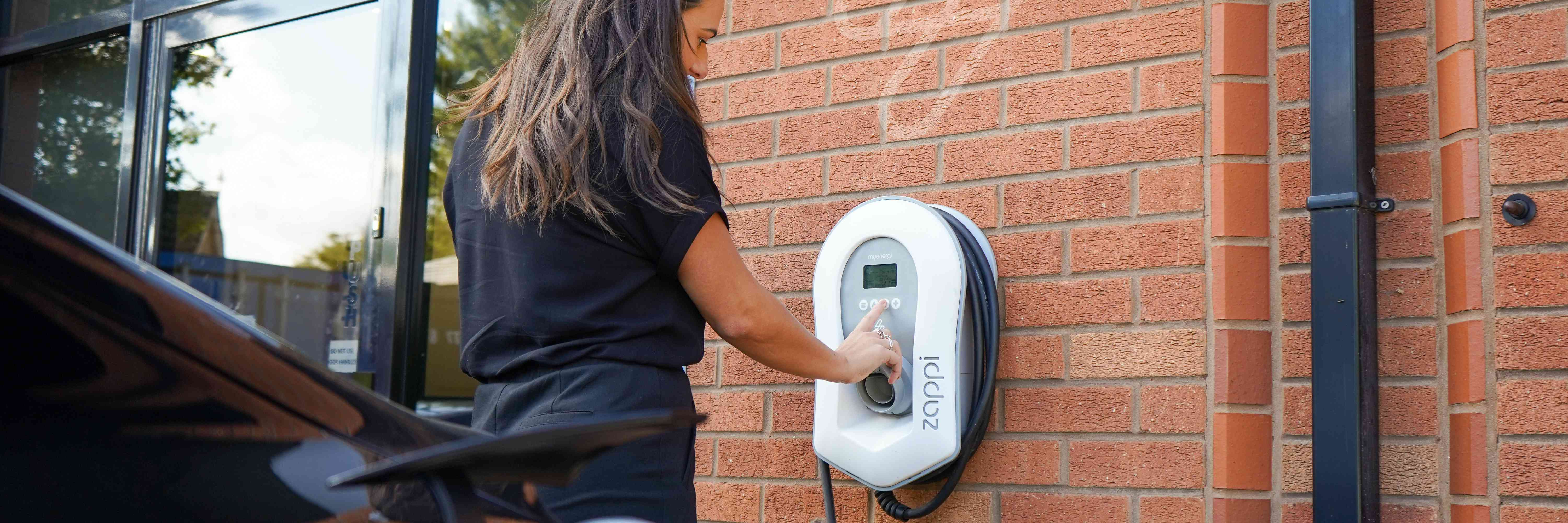 Woman using a public electric vehicle charger