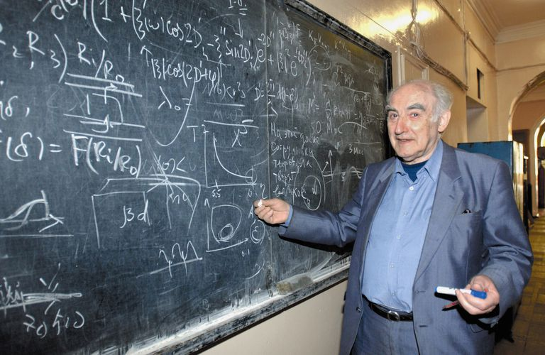 Picture of physicist Vitaly Ginzburg writing formulas on a chalkboard
