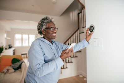 An older adult setting up a smart thermostat.