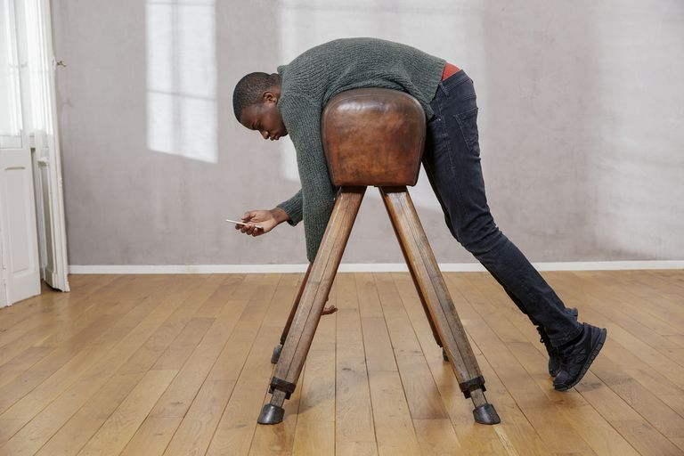 Young man hanging out on pommel horse looking at smartphone