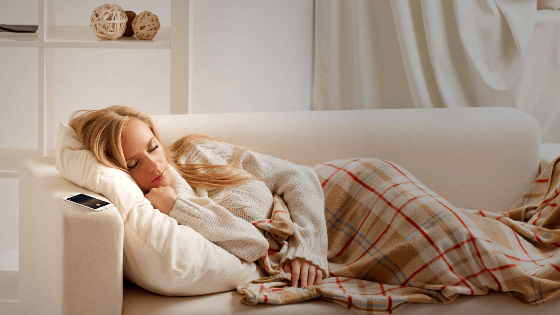 Woman sleeping on her couch with the Pzizz app on her iPhone