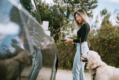 Asian woman charging her car and holding leash for Golden Retriever.