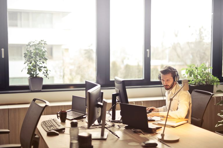 A man wearing headphones while sitting at a desk.