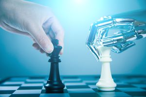 Human hand holding chess piece and metal android hand holding chess piece representing computer chess game