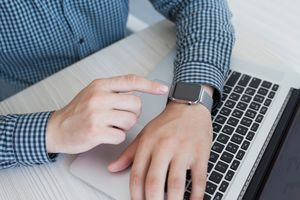 A man using an Apple Watch and a Mac laptop.
