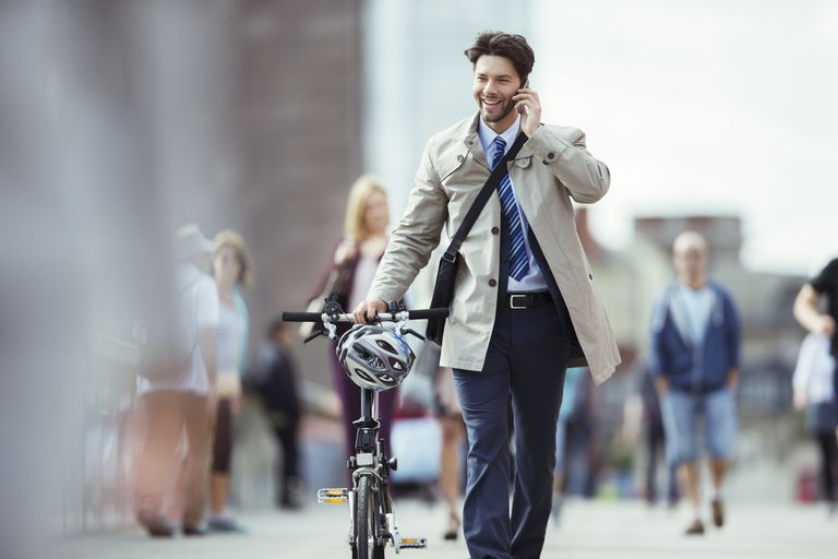 A businessman talking on a cellphone and pushing a bike as he walks through the city.