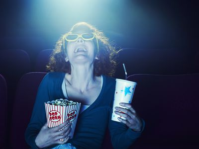 Woman wearing sunglasses laughing and holding a drink and popcorn while sitting in a movie theater.
