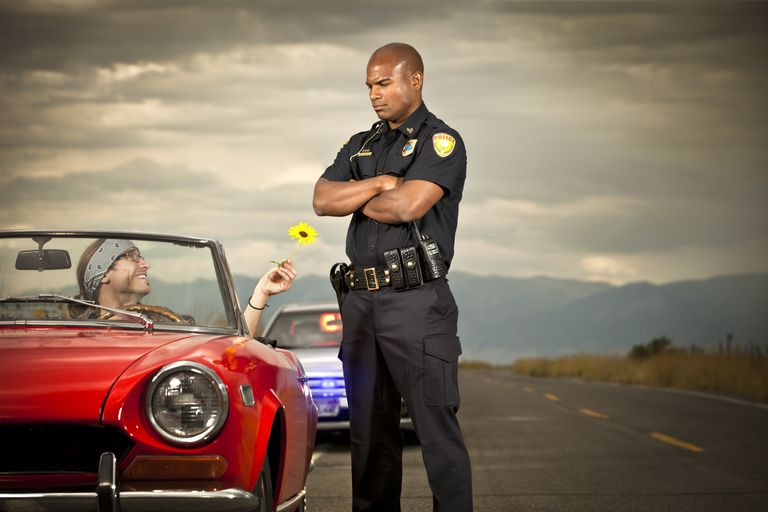 Picture of a police officer next to a stopped red vehicle with a man holding a flower